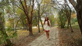 Κορίτσι σε ένα άσπρο παλτό, με τη μακριά κόκκινη τρίχα, που σκουπίζει το πάρκο φθινοπώρου λεωφόρων απόθεμα βίντεο