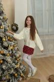 κορίτσι σε ένα άσπρο πουλόβερ κοντά στο χριστουγεννιάτικο δέντρο στοκ εικόνες