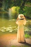Κορίτσι σε ένα άσπρο φόρεμα και καπέλο στην ακτή μιας λίμνης με το ύδωρ στοκ εικόνα