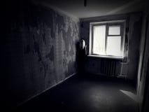 Κορίτσι σε ένα εγκαταλειμμένο ανατριχιαστικό δωμάτιο στοκ φωτογραφίες
