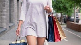 Κορίτσι σε ένα ελαφρύ φόρεμα με τα μακρυμάλλη πακέτα peset με τις αγορές στα χέρια μετά από να ψωνίσει κίνηση αργή HD απόθεμα βίντεο