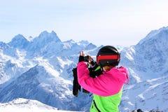 Κορίτσι σε ένα ζωηρόχρωμο κοστούμι που φωτογραφίζεται πάνω από ένα χιονώδες βουνό στοκ εικόνες