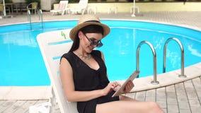 Κορίτσι σε ένα καπέλο αχύρου με μια ταμπλέτα κοντά στη λίμνη φιλμ μικρού μήκους