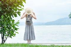 Κορίτσι σε ένα καπέλο με ένα σακίδιο πλάτης που στέκεται σε μια αποβάθρα στη θάλασσα Mou στοκ φωτογραφία