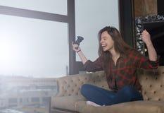 Κορίτσι σε ένα κόκκινο πουκάμισο στον καναπέ Στοκ Εικόνες
