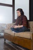 Κορίτσι σε ένα κόκκινο πουκάμισο στον καναπέ Στοκ Φωτογραφίες