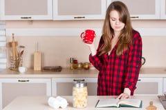 Κορίτσι σε ένα κόκκινο πουκάμισο των ατόμων κουζίνα με το φλυτζάνι τα χέρια του Στοκ Φωτογραφία