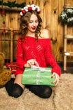 Κορίτσι σε ένα κόκκινο δώρο Χριστουγέννων ανοίγματος πουλόβερ νέο έτος έννοιας Στοκ Εικόνες
