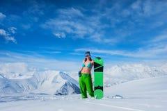 Κορίτσι σε ένα μαγιό με έναν πίνακα σνόουμπορντ στο κλίμα Στοκ Φωτογραφία