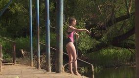 Κορίτσι σε ένα μαγιό που πηδά από την αποβάθρα στο νερό απόθεμα βίντεο