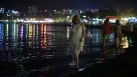 Κορίτσι σε ένα μακρύ άσπρο φόρεμα περίπατοι κατά μήκος της παραλίας τη νύχτα απόθεμα βίντεο