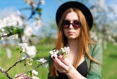 Κορίτσι σε ένα μαύρο καπέλο και το ανθίζοντας Apple-δέντρο Στοκ Φωτογραφία