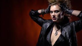 Κορίτσι σε ένα μαύρο σακάκι δέρματος, που θέτει και που κρατά την τρίχα της, πανκ rocker γυναίκα απόθεμα βίντεο