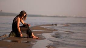 Κορίτσι σε ένα μαύρο φόρεμα και τα γυαλιά ηλίου που κάθονται σε έναν βράχο στην παραλία και που ρίχνουν ένα χαλίκι στο νερό απόθεμα βίντεο
