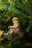 Κορίτσι σε ένα ποδήλατο - παιχνίδι γούνα-δέντρων στους κλάδους ενός ζωντανού χριστουγεννιάτικου δέντρου Στοκ εικόνες με δικαίωμα ελεύθερης χρήσης
