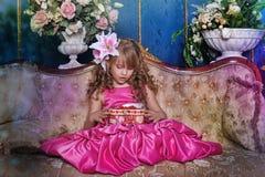 Κορίτσι σε ένα ρόδινο φόρεμα μεταξύ των λουλουδιών Στοκ Εικόνες