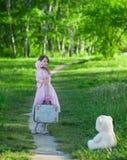 Κορίτσι σε ένα ρόδινο φόρεμα με μια βαλίτσα που περπατά κατά μήκος της δασικής πορείας Στοκ Εικόνες
