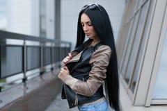 Κορίτσι σε ένα σακάκι δέρματος που στέκεται κοντά στο κτήριο Στοκ Φωτογραφία