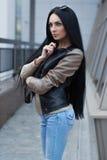 Κορίτσι σε ένα σακάκι δέρματος που στέκεται κοντά στο κτήριο Στοκ Εικόνες