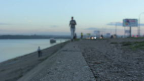 Κορίτσι σε ένα σκούντημα βραδιού Νέα γυναίκα που τρέχει στην πόλη στο φράγμα, κοντά στο νερό απόθεμα βίντεο