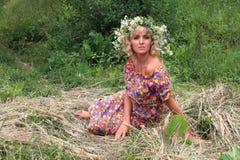 κορίτσι σε ένα στεφάνι των λουλουδιών στη φάτνη Στοκ εικόνες με δικαίωμα ελεύθερης χρήσης