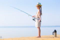 Κορίτσι σε ένα φόρεμα και ένα καπέλο με μια ράβδο αλιείας Στοκ Φωτογραφία