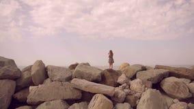 Κορίτσι σε ένα φόρεμα που στέκεται πάνω από ένα βουνό και που εξετάζει την απόσταση σε αργή κίνηση απόθεμα βίντεο