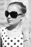 Κορίτσι σε ένα φόρεμα Πόλκα-σημείων και αναδρομικά γυαλιά Στοκ Εικόνες