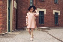 Κορίτσι σε ένα όμορφα ρόδινα φόρεμα και ένα μαύρο καπέλο Τα ταξίδια κοριτσιών Κορίτσι στο γύρο στην Ευρώπη Κορίτσι που περπατά μέ στοκ εικόνες