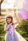 Κορίτσι σε ένα όμορφο πορφυρό παιχνίδι φορεμάτων με τα μπαλόνια στο πάρκο Στοκ Εικόνες