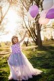 Κορίτσι σε ένα όμορφο πορφυρό παιχνίδι φορεμάτων με τα μπαλόνια στο πάρκο Στοκ εικόνες με δικαίωμα ελεύθερης χρήσης