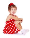 Κορίτσι σε μια κόκκινη συνεδρίαση φορεμάτων Πόλκα-σημείων στο πάτωμα Στοκ Φωτογραφίες