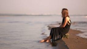 Κορίτσι σε μια μαύρη συνεδρίαση φορεμάτων σε έναν βράχο από τα πόδια ποταμών στο νερό φιλμ μικρού μήκους