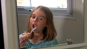 Κορίτσι σε μια μπλε μπλούζα που βουρτσίζει τα δόντια της φιλμ μικρού μήκους