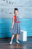 Κορίτσι σε μια ριγωτή βαλίτσα εκμετάλλευσης φορεμάτων Στοκ φωτογραφία με δικαίωμα ελεύθερης χρήσης