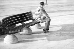 Κορίτσι σε μια ριγωτή συνεδρίαση φορεμάτων στον πάγκο Στοκ φωτογραφία με δικαίωμα ελεύθερης χρήσης