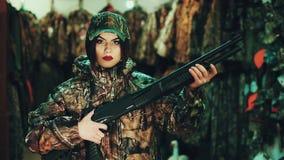 Κορίτσι σε μια στρατιωτική στολή και με ένα κυνηγετικό όπλο αντλία-δράσης Τοποθέτηση στη κάμερα απόθεμα βίντεο
