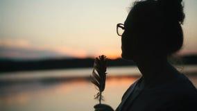 Κορίτσι σκιαγραφιών στα γυαλιά με ένα ηλιοβασίλεμα φτερών απόθεμα βίντεο