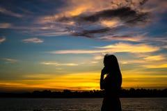 Κορίτσι σκιαγραφιών στο ηλιοβασίλεμα Στοκ Εικόνες