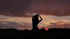 Κορίτσι σκιαγραφιών στο φόρεμα που χορεύει σε μια καλή διάθεση σε έναν τομέα σίτου το βράδυ απόθεμα βίντεο