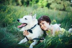 κορίτσι σκυλιών αυτή που αγκαλιάζει τις νεολαίες Στοκ Εικόνες