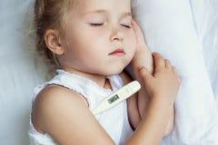κορίτσι σπορείων λίγη μητέρα κοντά στο άρρωστο θερμόμετρο συνεδρίασης Στοκ Εικόνες