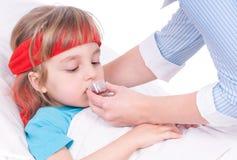κορίτσι σπορείων λίγη μητέρα κοντά στο άρρωστο θερμόμετρο συνεδρίασης Στοκ φωτογραφία με δικαίωμα ελεύθερης χρήσης