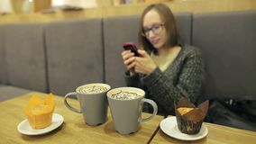 Κορίτσι σπουδαστών έκπληκτη σε γυαλιά χρησιμοποίηση από το μήνυμα κειμένου από το φίλο της Αυτή που χρησιμοποιεί app στο smartpho απόθεμα βίντεο