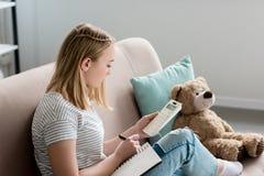 κορίτσι σπουδαστών εφήβων που γράφει στο σημειωματάριο και που χρησιμοποιεί τον υπολογιστή καθμένος στοκ εικόνες
