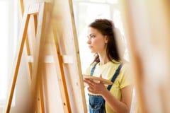 Κορίτσι σπουδαστών με easel τη ζωγραφική στο σχολείο τέχνης Στοκ Εικόνες