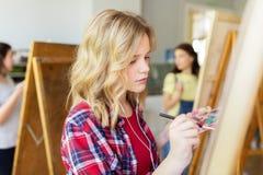 Κορίτσι σπουδαστών με easel τη ζωγραφική στο σχολείο τέχνης Στοκ εικόνα με δικαίωμα ελεύθερης χρήσης