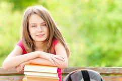 Κορίτσι σπουδαστών στον πάγκο και το χαμόγελο στοκ φωτογραφίες