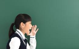 Κορίτσι σπουδαστών εφήβων που φωνάζει πριν από τον πίνακα κιμωλίας στοκ φωτογραφία με δικαίωμα ελεύθερης χρήσης