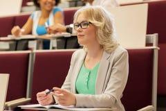 Κορίτσι σπουδαστών που γράφει στο σημειωματάριο στην αίθουσα διάλεξης στοκ εικόνες